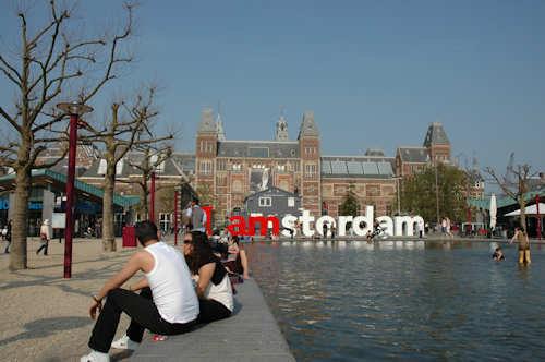 Folk koser seg i solen på Museumsplein foran Rijksmuseum i Amsterdam — Foto: Gaute Nordvik
